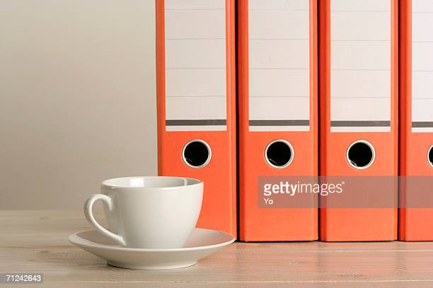 Cup of coffee in front of folders