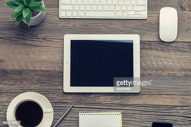 Cup of coffee , keyboard and digital tablet on wooden table.