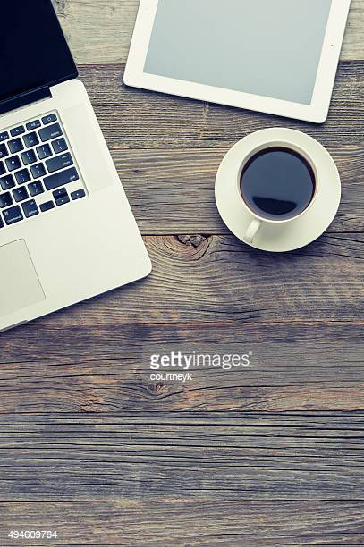 Cup of coffee, laptop and digital tablet on wooden table.