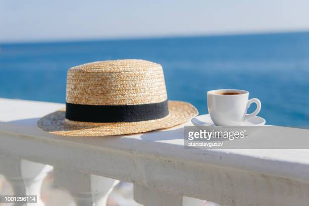 cup of coffee next to a straw hat on a wall - straw hat stock pictures, royalty-free photos & images
