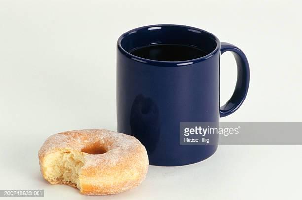 Cup of coffee next to Bitten Doughnut, (Close-up)
