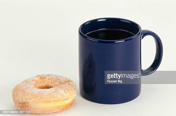 Cup of coffee next to doughnut