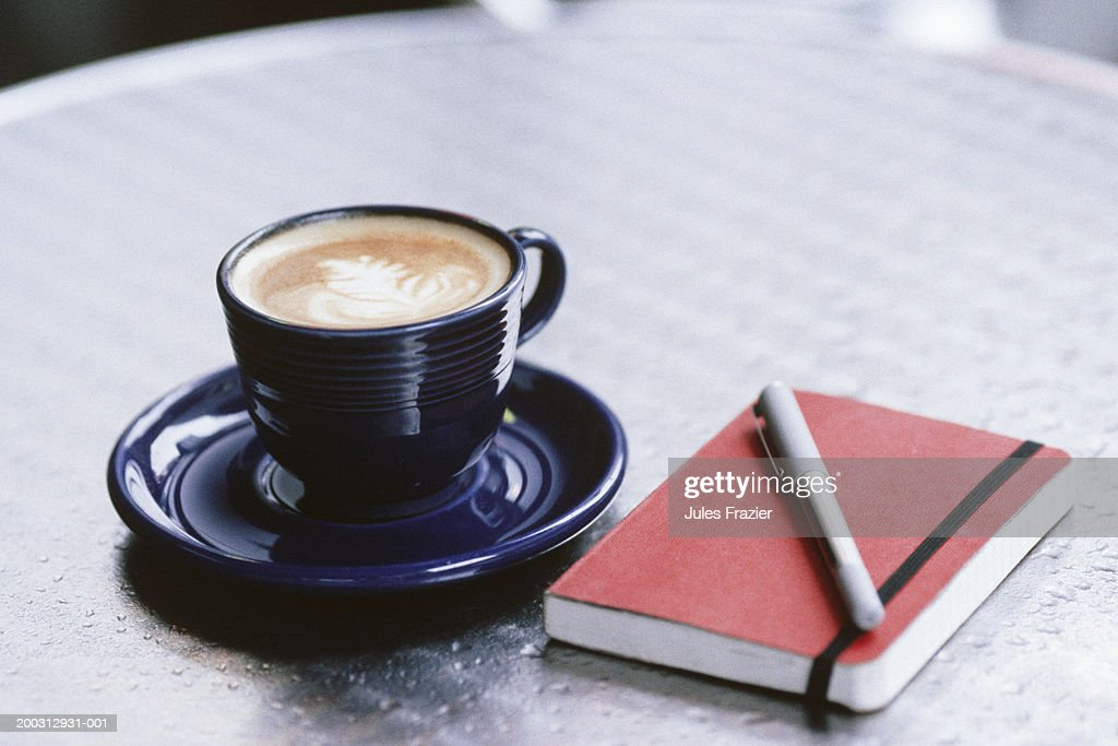 Cup of coffee, notebook and pen lying on table : Foto stock