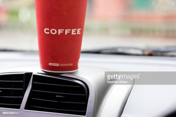 A cup of coffee on a dashboard. A concept of lifestyle.