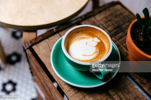 cup of coffee on a wooden table - coffee shop stock pictures, royalty-free photos & images