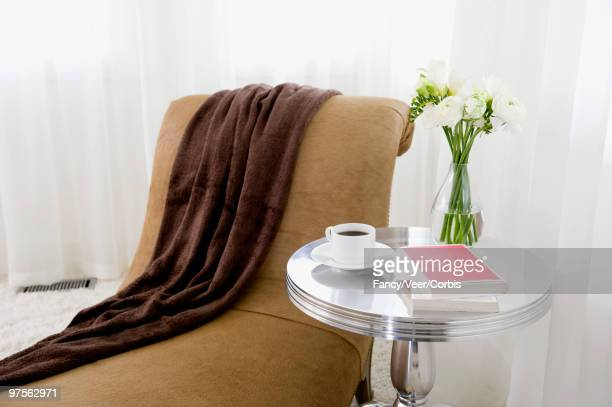Cup of coffee on end table next to chaise longue