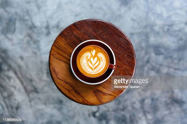 cup of coffee standing on a round coffee table - hot love stock pictures, royalty-free photos & images