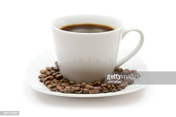 Cup of coffee surrounded by coffee beans on white saucer