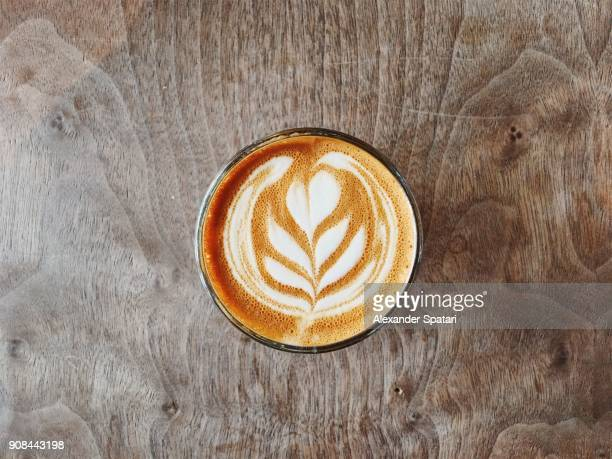 Cup of coffee with beautiful latte art on the wooden table