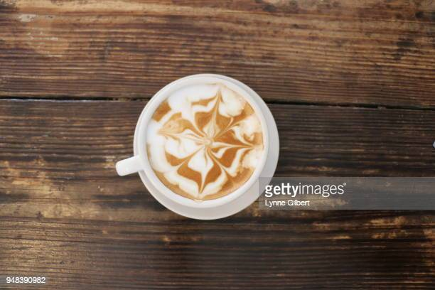 a cup of coffee with foam on top has a beautiful design - wood table top stock photos and pictures