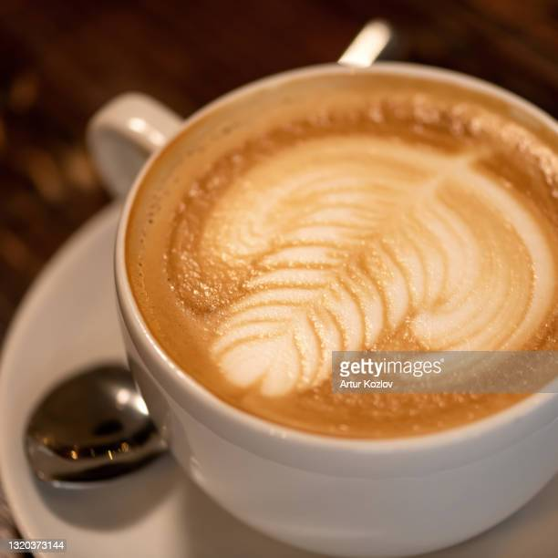 cup of coffee with milk. close up of cappuccino with art on creamy foam. rest break from business with natural energy drink. foam drawing. soft focus - coffee drink stock pictures, royalty-free photos & images