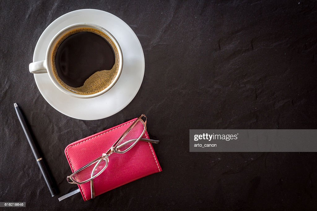 Cup of coffee with notebook and pen on black background : Foto stock