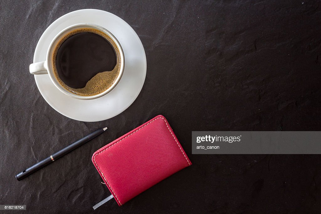 Cup of coffee with notebook and pen on black background : Bildbanksbilder