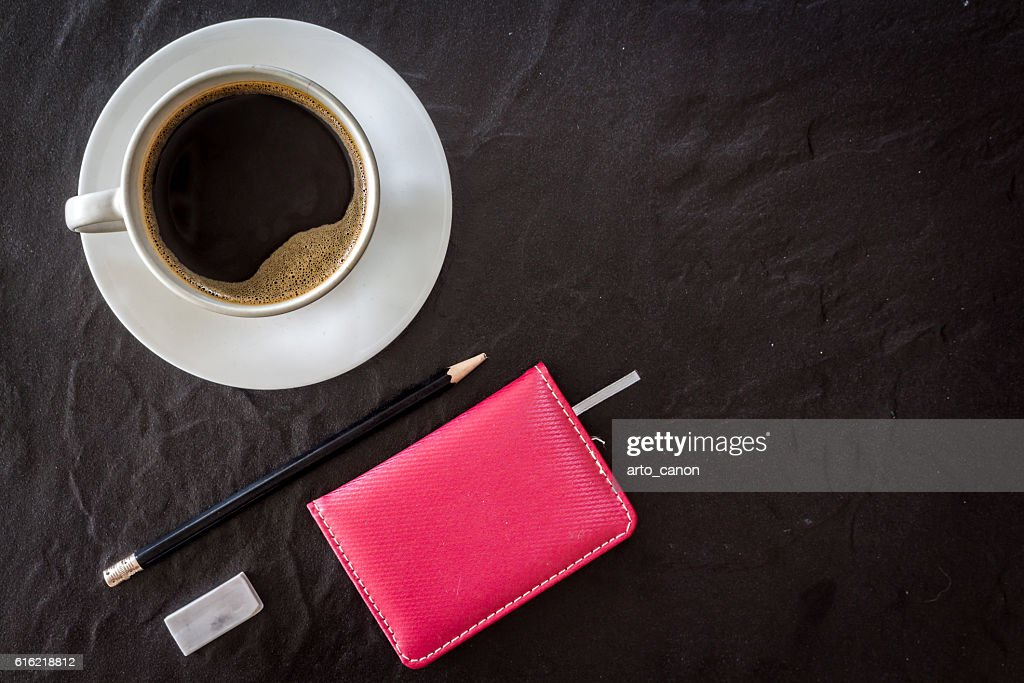 Cup of coffee with notebook and pen on black background : Stockfoto
