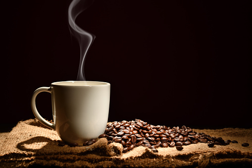 Cup of coffee with smoke and coffee beans on black background 924005570