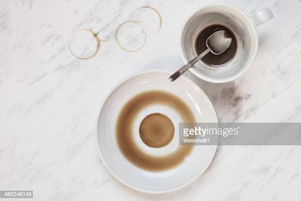 Cup of coffee with vestiges of coffee on white marble panel