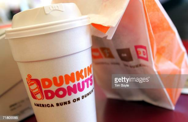 A cup of Dunkin' Donuts coffee and a donut bag sit on a counter September 7 2006 in Chicago Illinois In an effort to compete with Starbucks in the...