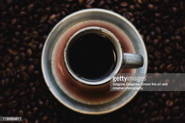 a cup of espresso coffee sitting on top of a layer of coffee beans - gregoria gregoriou crowe fine art and creative photography. fotografías e imágenes de stock