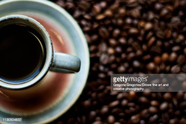 a cup of espresso coffee sitting on top of a layer of coffee beans - gregoria gregoriou crowe fine art and creative photography. stock pictures, royalty-free photos & images