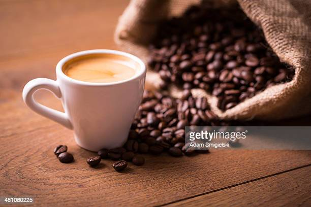 cup of espresso shot with coffee beans on wooden table - espresso stock photos and pictures