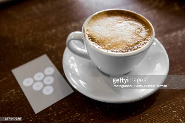 A cup of flat white coffee made with oat milk and a loyalty card in coffee shop.