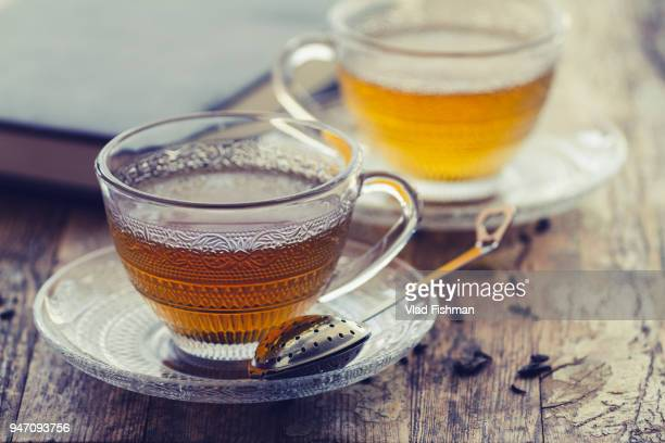 cup of green tea on a vintage rustic wood blurry or bokeh background - tea leaves stock photos and pictures