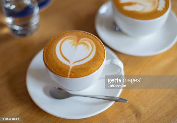 cup of hot cappuccino -  latte art coffee on wooden table - cappuccino stock pictures, royalty-free photos & images