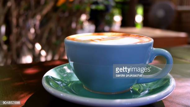Cup of hot coffee in morning and green nature background .
