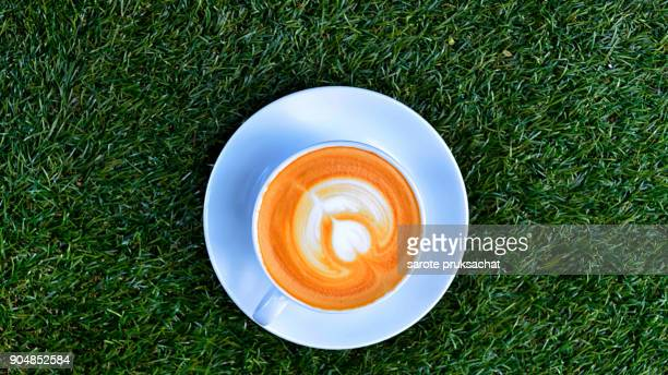 Cup of hot coffee on  green artificial grass  background .