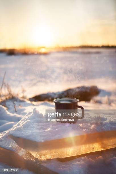 Cup of hot coffee on snow, winter sunny day  background