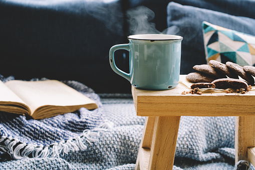 Cup of hot drink on wooden table. Living room interior with blue sofa on background. 1066951228