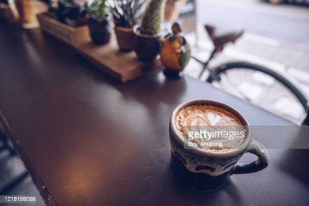 a cup of hot latte coffee on the table nearly window. - smooth stock pictures, royalty-free photos & images