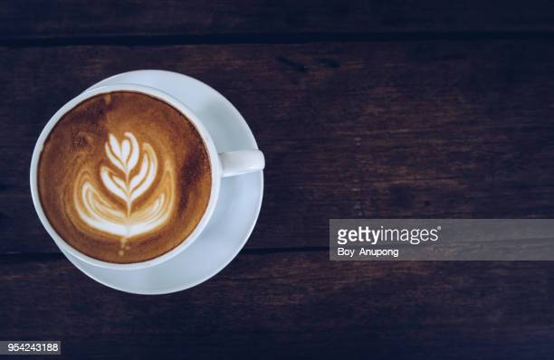 a cup of hot latte coffee on the wooden table from high angle view. - latte stock pictures, royalty-free photos & images