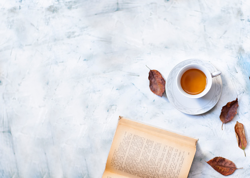A cup of hot tea with fall leaves and copy space 1169898207
