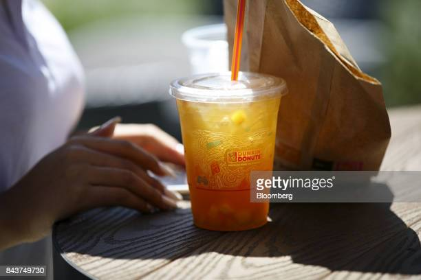 Cup of iced tea sits next to a customer outside a Dunkin' Donuts Inc. Location in Los Angeles, California, U.S., on Wednesday, Sept. 6, 2017. Dunkin'...