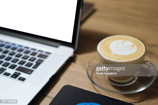 Cup of latte art coffee and Laptop on wood table