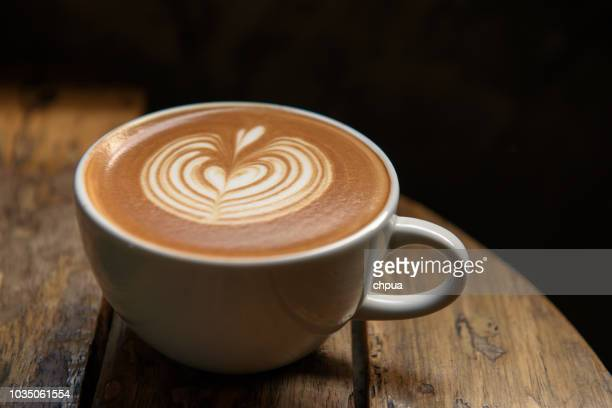 a cup of latte on wooden table - coffee stock pictures, royalty-free photos & images