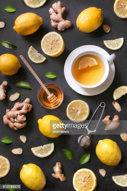 A cup of lemon ginger honey tea on rustic wooden background.