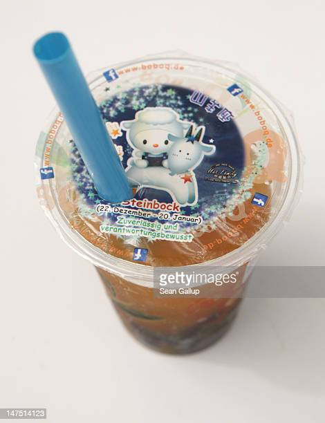 A cup of mangoflavoured bubble tea stands at a bubble tea cafe on June 29 2012 in Berlin Germany Bubble tea which fuses Asian tea with milk or fruit...