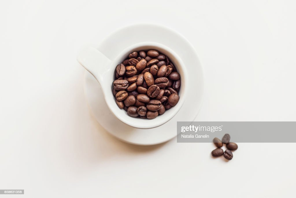 Cup of roasted coffee beans on white : Stock-Foto
