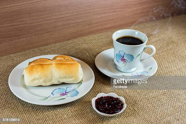 Cup of steaming coffee, bread, butter and jam