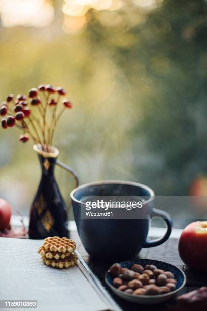 cup of steaming tea, book, cookies and autumnal decoration on window sill - hygge stock pictures, royalty-free photos & images