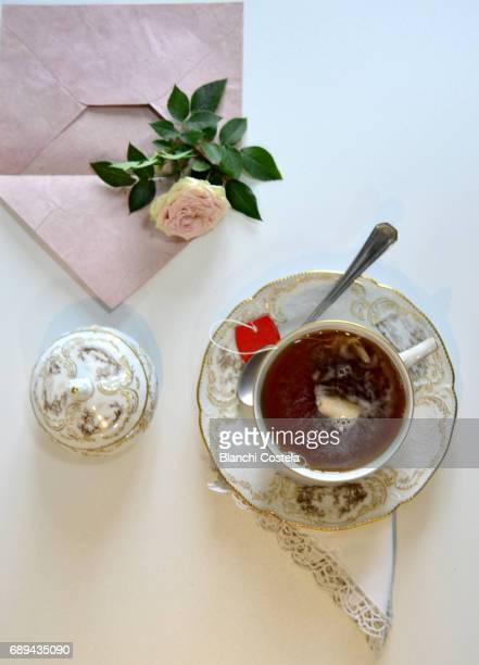Cup of tea and flower seen from above in white background