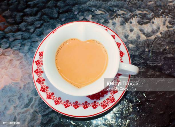 cup of tea in heart shape cup - lyn holly coorg stock-fotos und bilder