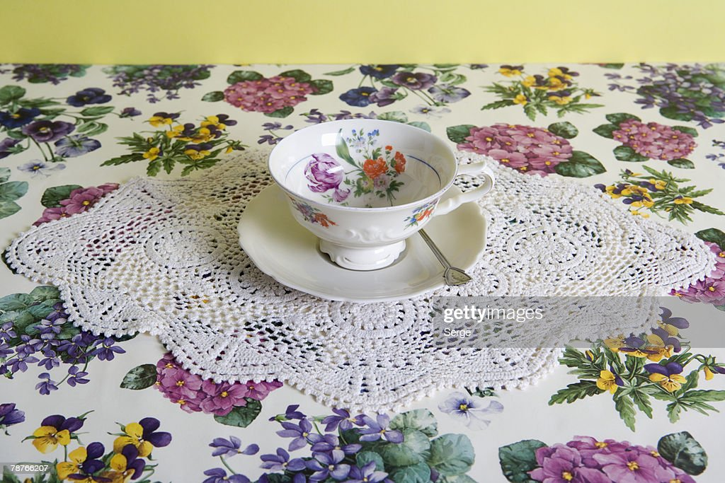 A cup of tea on a floral tablecloth : Stock Photo