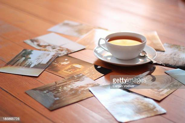 Cup of tea on a wooden floor surrounded by photos
