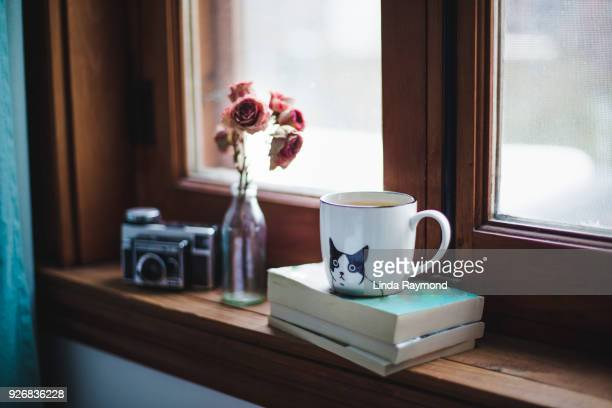 A cup of tea on books with dried roses on a window sill