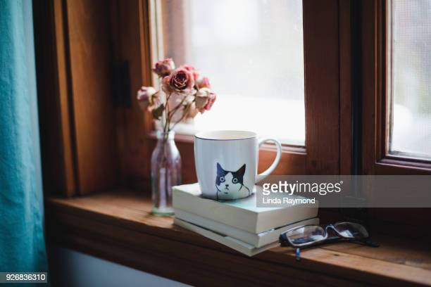 a cup of tea on books with dried roses on a window sill - window sill stock pictures, royalty-free photos & images