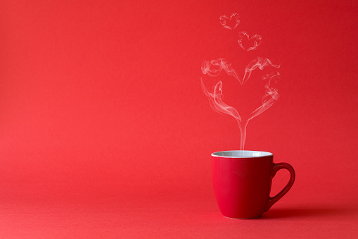 Cup of tea or coffee with steam in one heart shape on red background. Valentine's day celebration or love concept. Copy space 1081588494