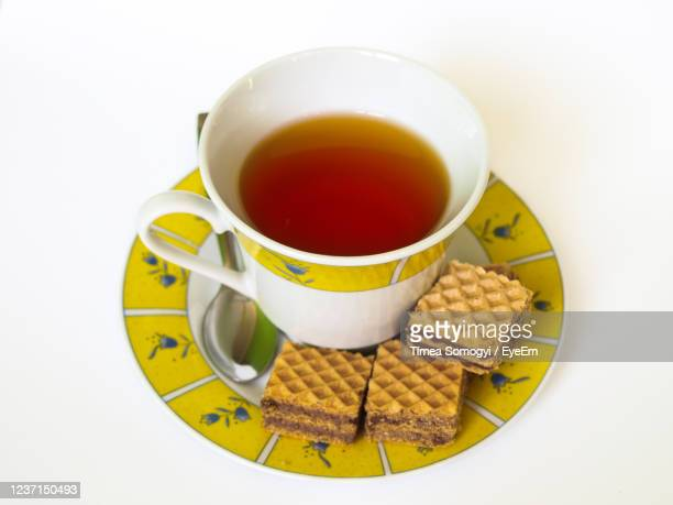 cup of tea with chocolate wafers, metal teaspoon, floral plate, on white isolated background. - saucer stock pictures, royalty-free photos & images